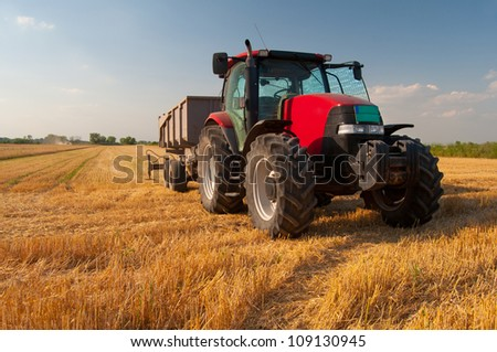 Modern red tractor on the agricultural field on sunny summer day.