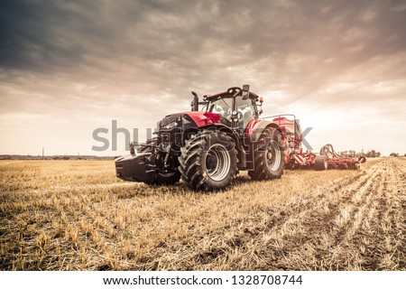 Modern red tractor seeding directly into the stubble with red equipment using GPS for precision farming in the fields of Czech Republic.