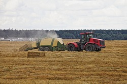 Modern red wheeled tractor with trailer picks up hay and presses hay into rectangular bricks on a yellow harvested field on an autumn day, agricultural machinery in farming, industrial rural landscape