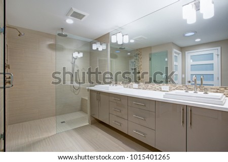 Modern refreshing bathroom features a beige dual washstand accented with mosaic backsplash beneath a full length vanity mirror placed next to a walk in shower finished with a glass partition.  #1015401265