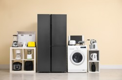 Modern refrigerator and other household appliances near beige wall indoors