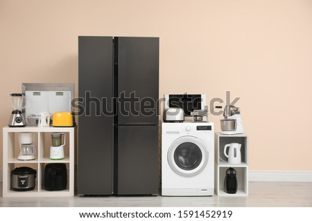 Modern refrigerator and other household appliances near beige wall indoors stock photo