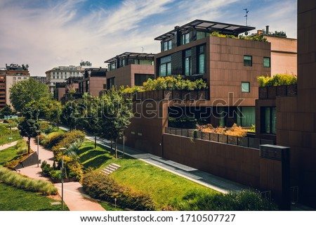 Modern residential buildings in the public green area. Apartment houses in Europe. Beautiful view of real estate homes in Milan, Italy. Business district in summer. Walking area with trees and grass. Foto stock ©