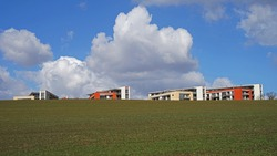 Modern residential flat buildings located on empty meadow behind major city, new living concept