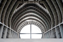 modern retro ceiling metal steel arch wall with round window light, part inside old airplane. abstract background