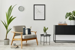 Modern retro concept of home interior with design grey armchair, coffee table, commode, plants, mock up poster map, carpet and personal accessoreis. Stylish home decor of living room.