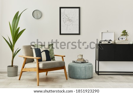 Modern retro concept of home interior with design grey armchair, coffee table, plants, mock up poster map, carpet and personal accessories. Stylish home decor of living room.