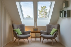 Modern retro design in a attic / loft. Small vintage table with a radio on and two reading chairs under two skylights. Roof / ceiling window.