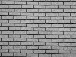 Modern rock stone wall background made of bricks on a wall of the building with rough texture and interesting antique retro natural pattern in black and white