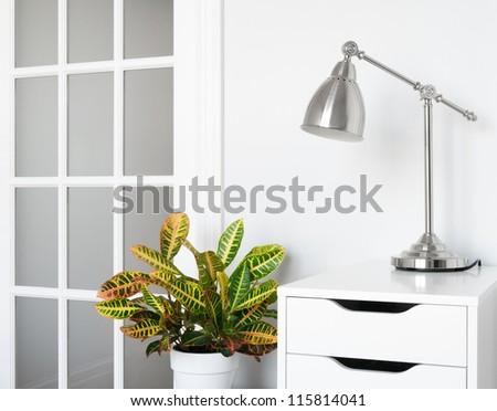 Modern room decor. Green plant, stylish furniture and lighting.