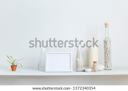Modern room decoration with picture frame mockup. Shelf against white wall with decorative candle, glass and rocks. Potted spider plant.