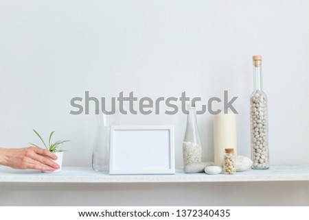 Modern room decoration with picture frame mockup. Shelf against white wall with decorative candle, glass and rocks. Hand putting down potted spider plant.