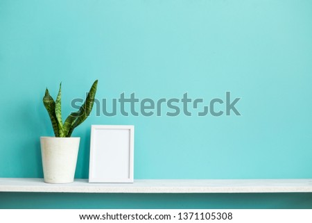 Modern room decoration with Picture frame mockup. White shelf against pastel turquoise wall with potted snake plant.