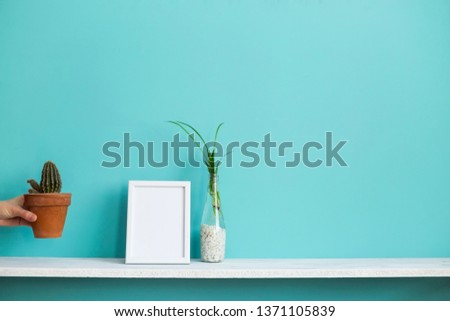 Modern room decoration with Picture frame mockup. White shelf against pastel turquoise wall with spider plant cuttings in water and hand putting down cactus.