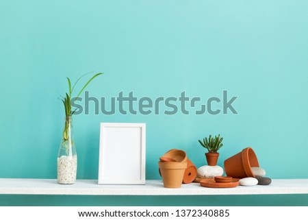Modern room decoration with picture frame mockup. White shelf against pastel turquoise wall with pottery and succulent plant with potted spider plant.