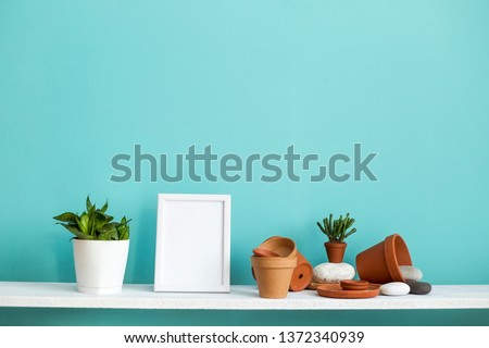 Modern room decoration with picture frame mockup. White shelf against pastel turquoise wall with pottery and succulent plant with potted snake plant.