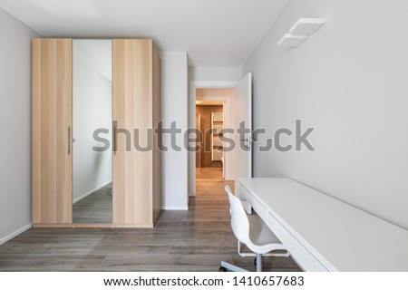 Modern room with closet, desk and office chair. Nobody inside
