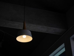 Modern round ceiling light with light bulb hanging from concrete construction in the dark room with copy space.