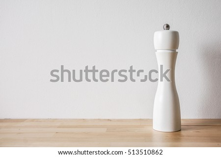 Modern salt grinder made of wood, painted white, standing on wood texture table, front view
