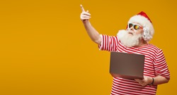 Modern Santa Claus on vacation working on laptop. Bright yellow background. Copy space. Christmas and New Year concept.