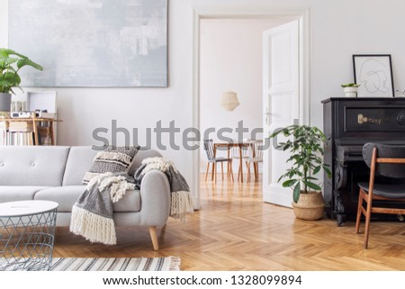 Modern scandianvian decor of living room with design sofa with elegant blanket, coffee table and bookstand on the white wall. Brown wooden parquet. Concept of minimalistic interior with piano. Mock up #1328099894