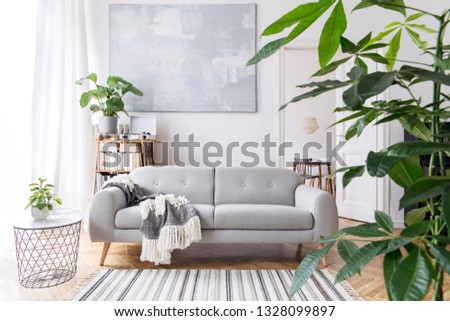 Modern scandianvian decor of living room with design sofa with elegant blanket, coffee table and bookstand on the white wall. Brown wooden parquet. Concept of minimalistic interior. #1328099897