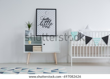 Modern Scandinavian child's bedroom interior with a small bed, monochromatic carpet, and a poster with text standing on a cupboard next to a plant #697082626