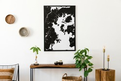 Modern scandinavian interior of living room with wooden console, avocado plant, armchair, lamp, basket and black elegant personal accessories. Stylish mock up poster map. Design home decor. Template.
