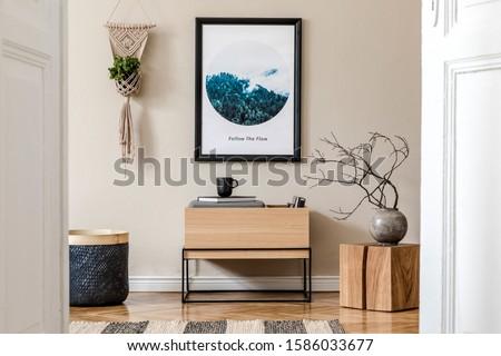 Modern scandinavian living room interior with black mock up poster frame, design commode, flowers in vase, black rattan basket, macrame, books and elegant accessories. Template. Stylish home staging.