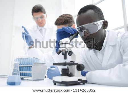 modern scientist looking through a microscope