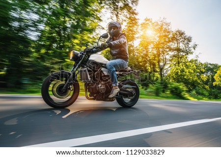 modern scrambler motorbike on the forest road riding. having fun driving the empty road on a motorcycle tour journey. Real dynamic motion blur shot. copyspace for your individual text. #1129033829