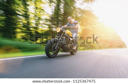 modern scrambler motorbike on the road riding a motorcycle at sunset. copyspace for your individual text. #1125367475
