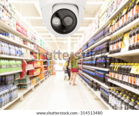 Modern security camera on monitoring the supermarket with blurred background