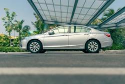 modern sedan car at outdoor parking lot with transparent roof, car parking shed at garage, selective focus