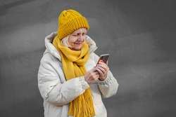 Modern senior woman in outerwear using smartphone. Contemporary elderly female in trendy outerwear smiling and browsing mobile phone while standing against blue wall on street