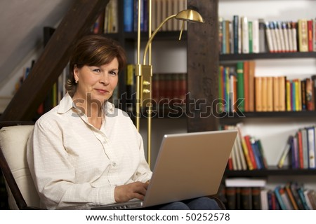 Modern senior woman sitting in front of bookshelf and working on laptop.