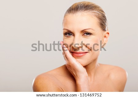 modern senior woman with hand on her face