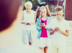 Modern serious kids spending time together outdoors using mobile gadgets