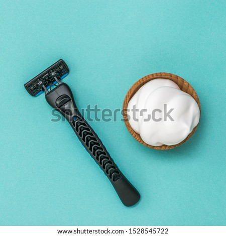 Modern shaving machine and shaving foam in wooden bowl on blue background. Set for care of a man's face. Flat lay.