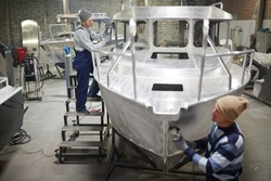 Modern shipbuilding engineers working over new boat in production factory