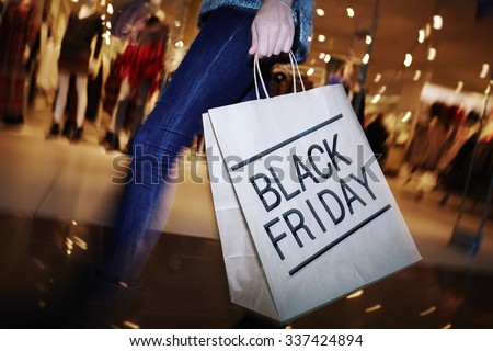 Modern shopper with Black Friday paperbag going in the mall #337424894