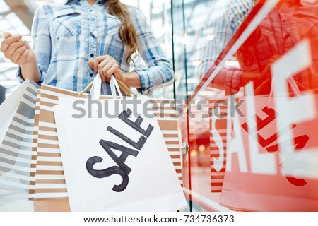 Modern shopper with sale paperbags standing in the mall