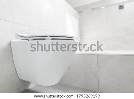 Modern Simplistic Design Of Bathroom With Large Ceramic Tile  And White Toilet Attached To Wall.  Photo stock ©