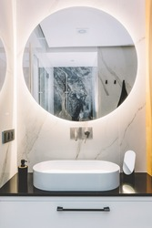 Modern sink and round mirror with led light in a luxury bathroom. Interior design