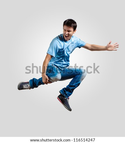 Modern slim hip-hop style man jumping dancing on a grey background - stock photo