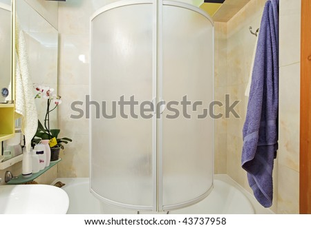 Modern small shower-bath with blue towel