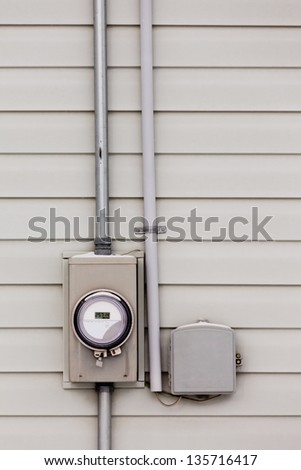 Modern smart grid residential digital power supply meter beside telecommunication connection box on exterior wall