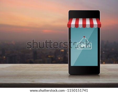 Modern smart mobile phone with online shopping store graphic and open sign on wooden table over blur of cityscape on warm light sundown, Business internet shop online concept