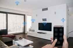 modern smarthome living room controlled by man holding a smartphone