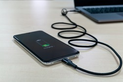 Modern smartphone are charging from the laptop on a light wooden table. Modern technology concept. Selective focus